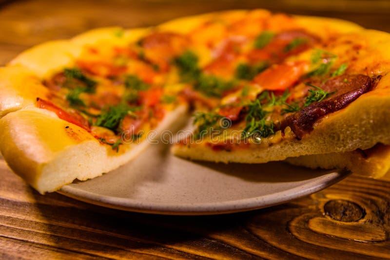 Piatto ceramico con pizza casalinga affettata su una tavola di legno fotografie stock