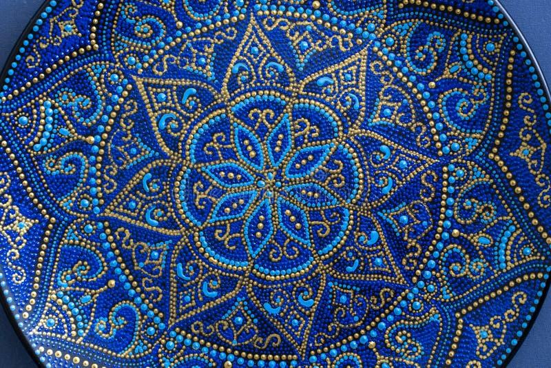 Piatto ceramico decorativo con i colori blu e dorati, piatti dipinti, primo piano Piatto decorativo della porcellana dipinto con  fotografia stock