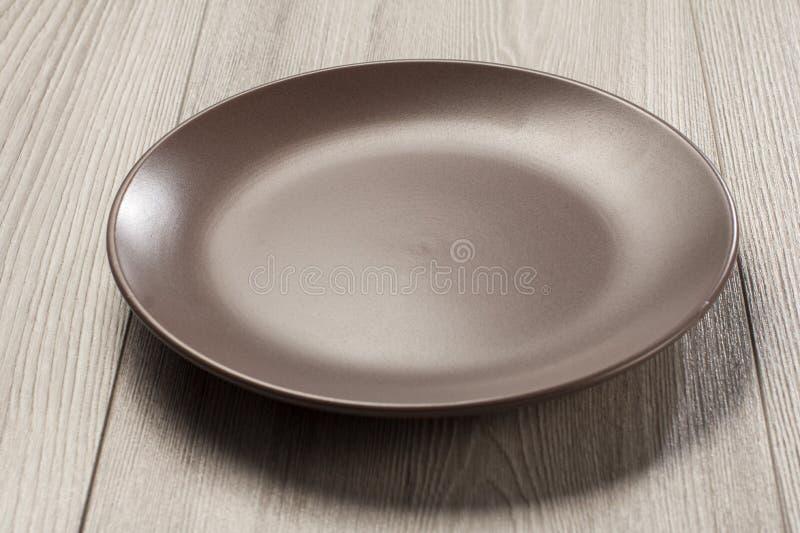 Piatto ceramico vuoto su fondo di legno grigio fotografia stock
