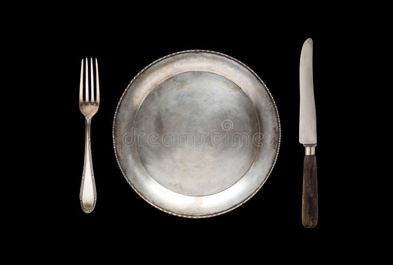 Piatto, coltello antico e forcella del metallo isolati su un fondo nero fotografie stock libere da diritti