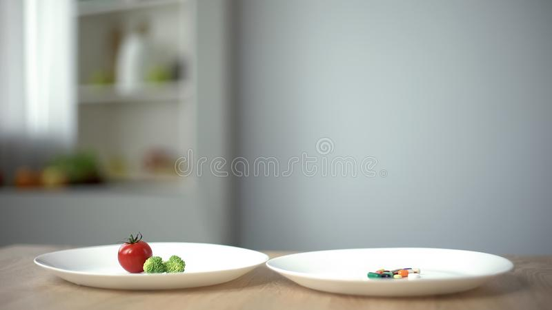 Piatto con alimento biologico contro le pillole per perdita di peso, scegliendo dieta sana o le droghe immagine stock libera da diritti