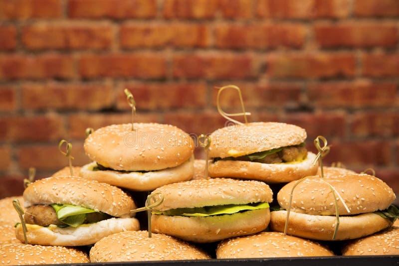 Piatto con gli hamburger contro un fondo del muro di mattoni immagine stock libera da diritti