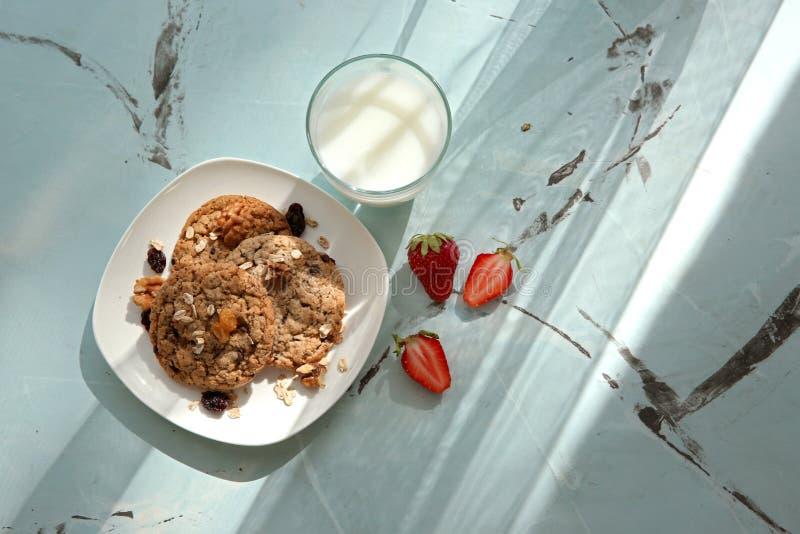 Piatto con i biscotti di farina d'avena deliziosi, il bicchiere di latte e la fragola fresca sulla tavola immagine stock