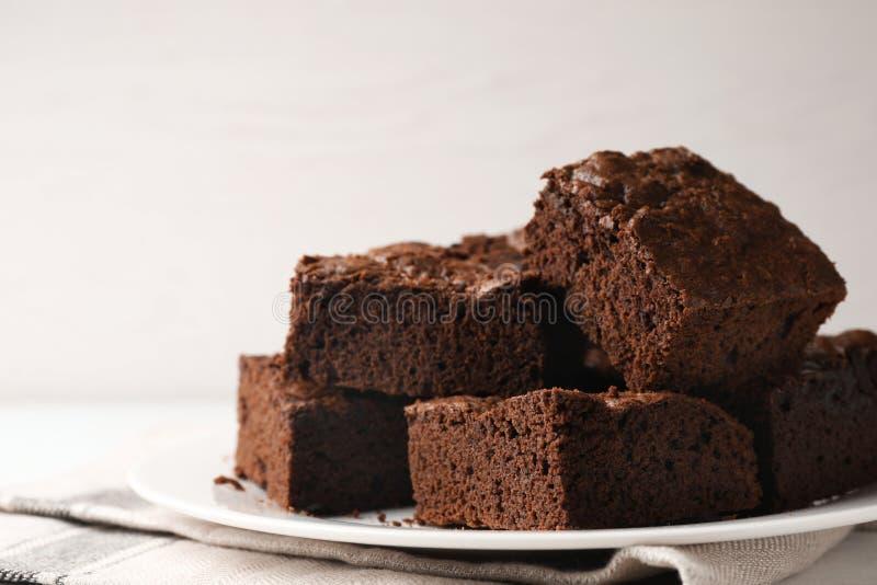 Piatto con i brownie freschi sulla tavola bianca contro fondo leggero Grafico a torta squisito del cioccolato fotografie stock