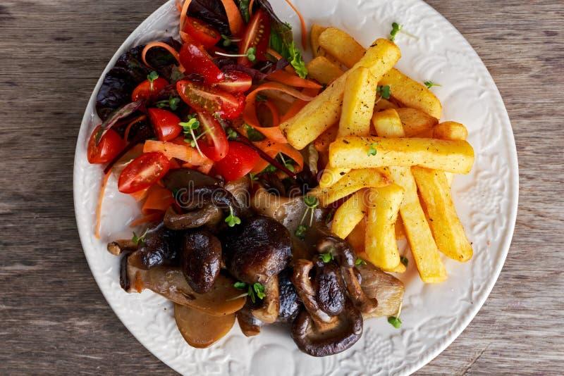 Piatto con i chip fritti, insalata del tomatoe, funghi selvaggi arrostiti di estate fotografia stock libera da diritti