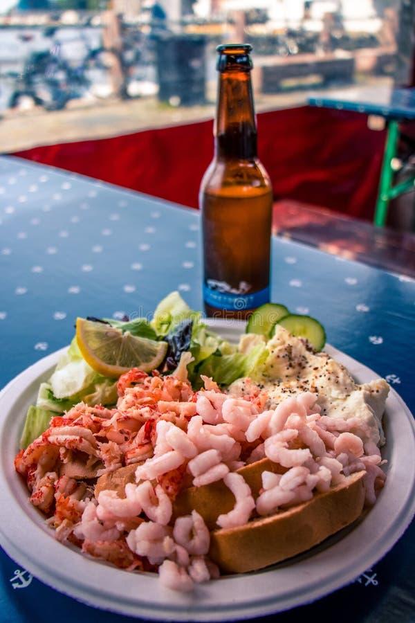 Piatto con i frutti di mare e una bottiglia di birra su una tavola immagine stock libera da diritti