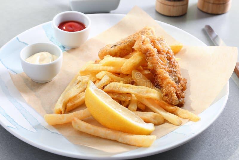 Piatto con il pesce, le patatine fritte e le salse fritti saporiti sulla tavola fotografie stock libere da diritti