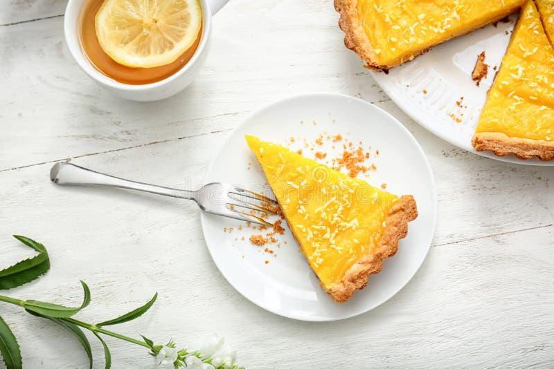 Piatto con il pezzo di torta del limone e di tazza saporite di tè sulla tavola di legno bianca immagine stock libera da diritti