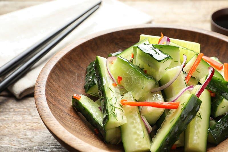 Piatto con l'insalata deliziosa del cetriolo sulla tavola immagini stock