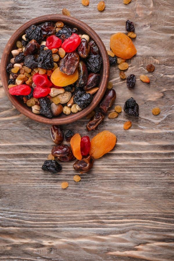 Piatto con la miscela dei frutti e delle bacche secchi su fondo di legno fotografie stock