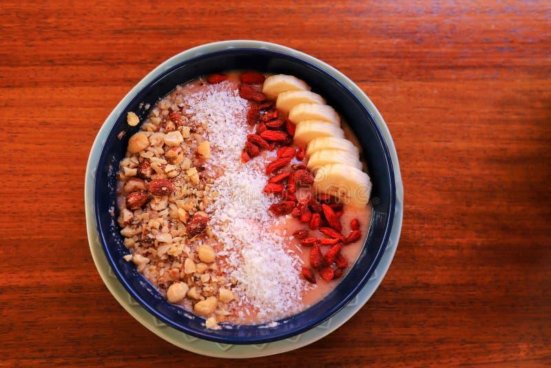 Piatto con la prima colazione di estate, macedonia su una tavola marrone Prima colazione del dado e della frutta - mousse dolce d fotografia stock libera da diritti