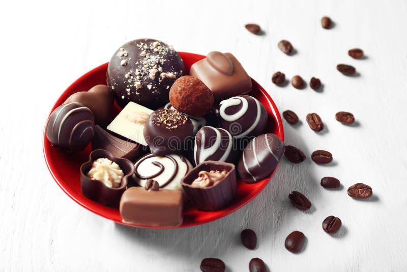Piatto con le caramelle di cioccolato ed i chicchi di caffè saporiti sulla tavola di legno fotografia stock libera da diritti