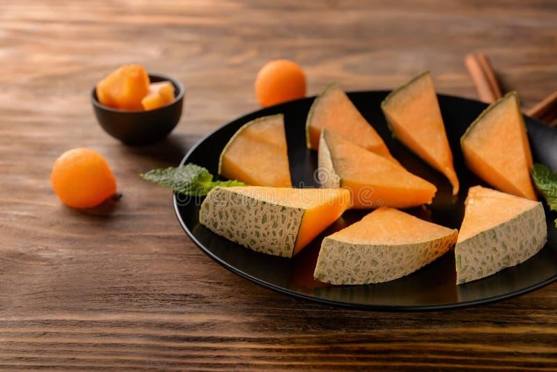 Piatto con le fette deliziose del melone sulla tavola di legno, primo piano immagini stock libere da diritti