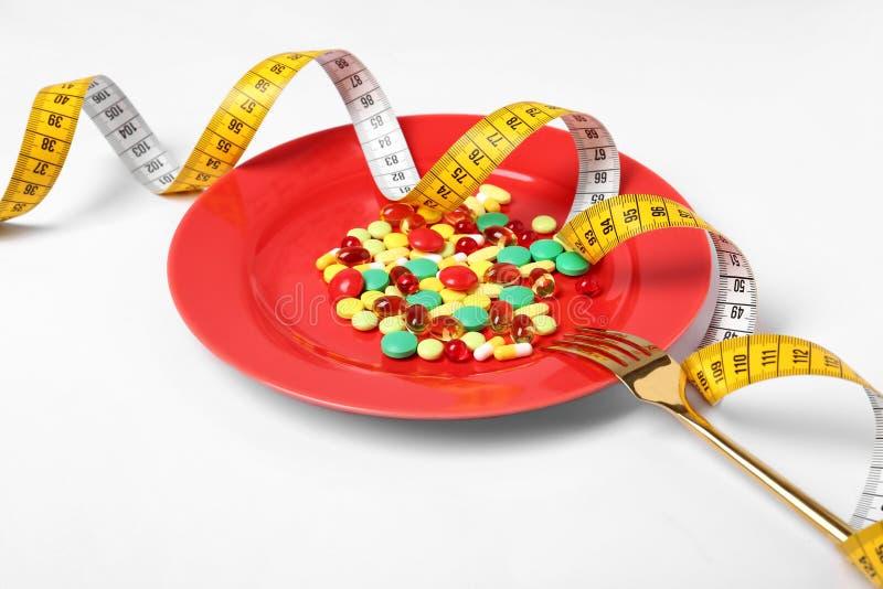 Piatto con le pillole di perdita di peso, la forcella e nastro adesivo di misurazione fotografia stock