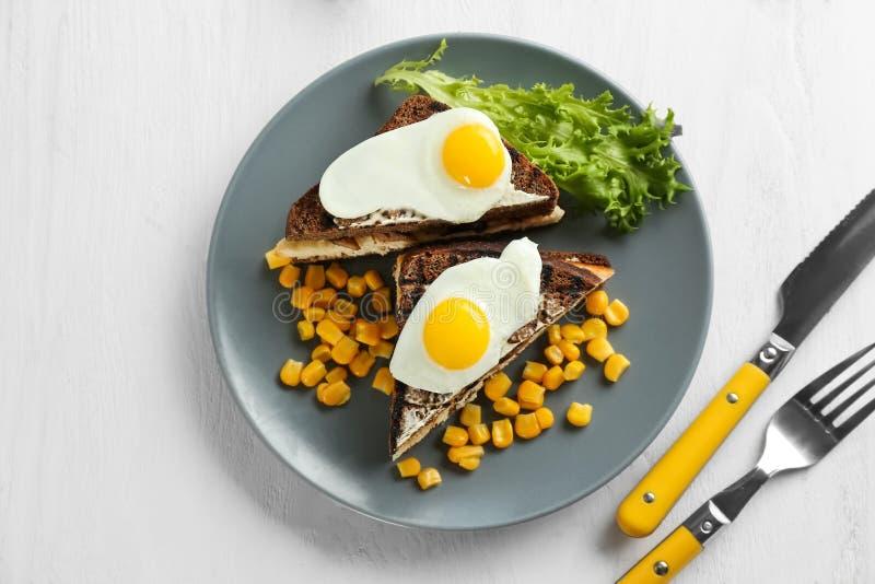 Piatto con pane tostato, le uova fritte ed i noccioli di cereale sulla tavola immagini stock libere da diritti