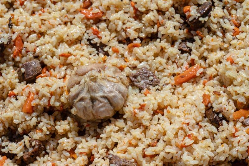 Piatto culinario asiatico tradizionale - pilaf Ingredienti: riso con le fette di carne, di grasso e di verdure carota, aglio, pop fotografia stock