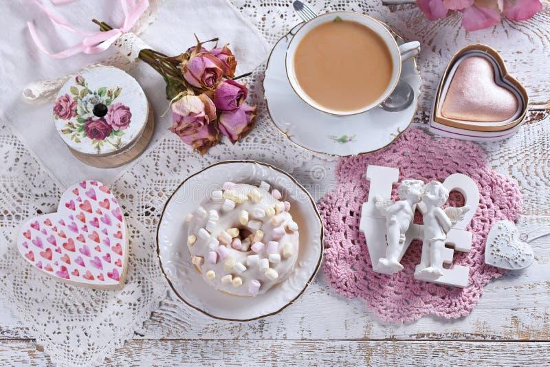 Piatto d'amore con una ciambella e una tazza di caffè fotografia stock