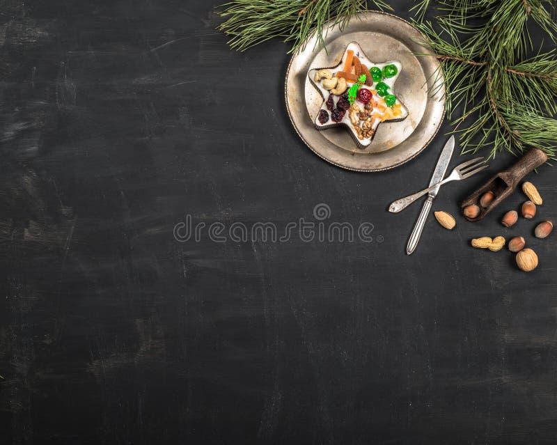 Piatto d'annata, cucchiaio e forchetta, dadi, dolci e rami del pino su fondo nero di legno immagini stock libere da diritti