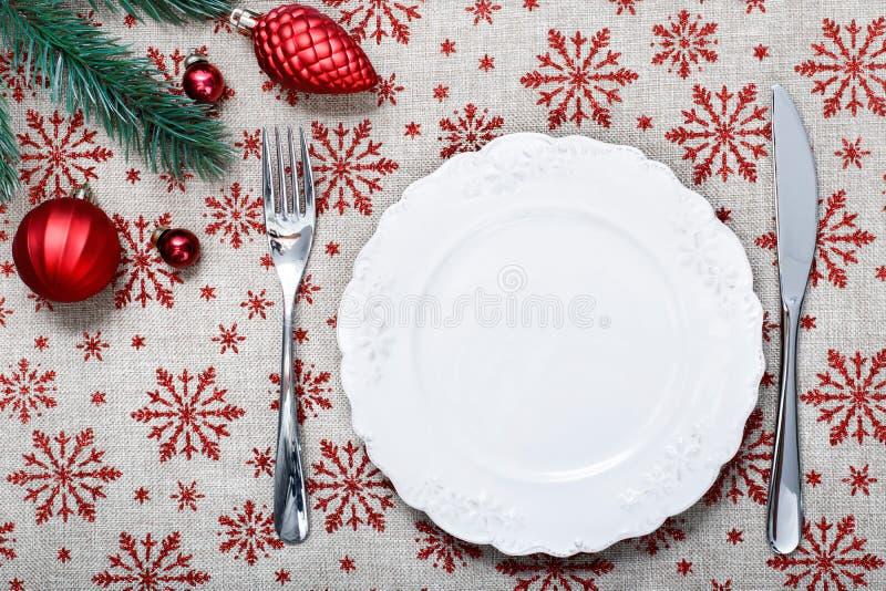 Piatto d'annata di Natale sul fondo di festa con gli ornamenti rossi di Natale Fondo della tela con i fiocchi di neve rossi di sc fotografia stock