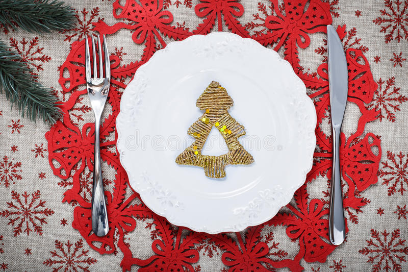 Piatto d'annata di Natale sul fondo di festa con l'albero di natale Fondo della tela con i fiocchi di neve rossi di scintillio Sc immagine stock
