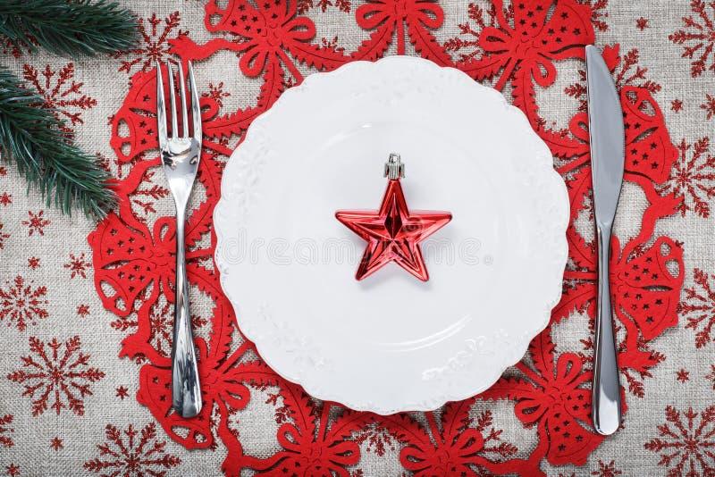 Piatto d'annata di Natale sul fondo di festa con la stella rossa Fondo della tela con i fiocchi di neve rossi di scintillio Sched fotografia stock libera da diritti