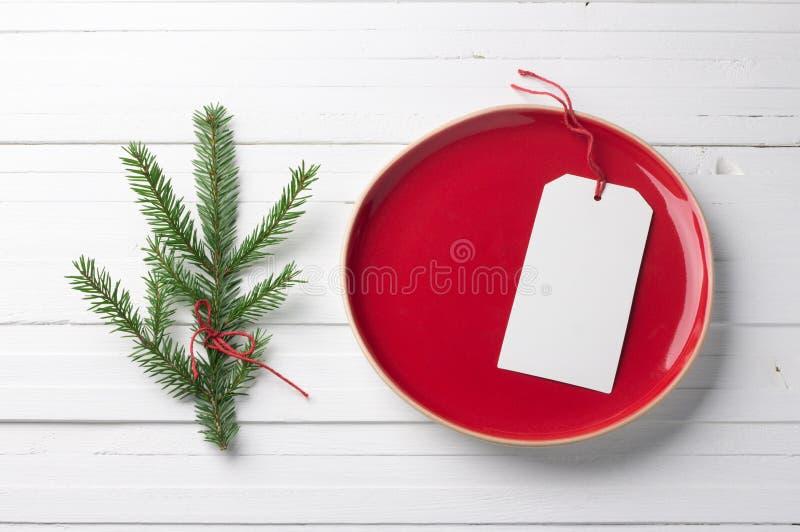 Piatto d'annata rosso con un'etichetta in bianco bianca e con un ramo di un albero di Natale immagini stock