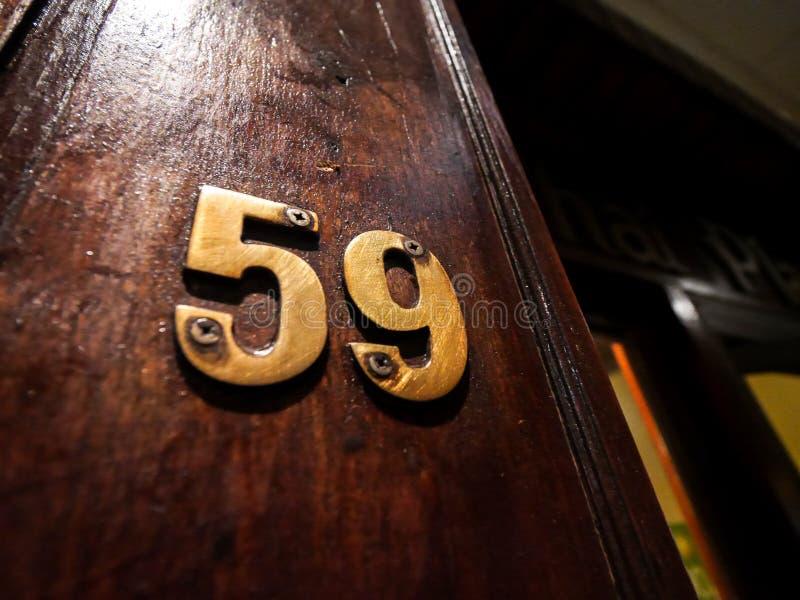 Piatto d'ottone di numero 59 sulla parete di legno immagine stock