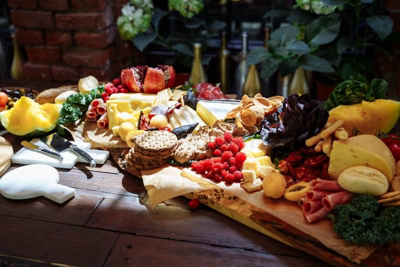 Piatto degli spuntini deliziosi di formaggio, del prosciutto di Parma, delle erbe fresche, dei frutti e delle bacche fotografia stock