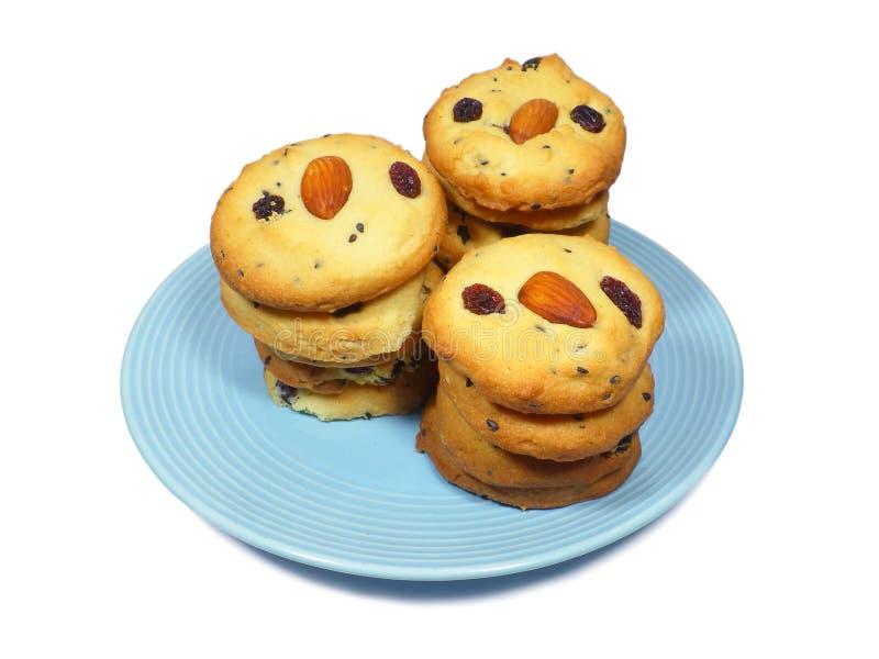 Piatto dei biscotti di burro su accatastati dell'uva passa della mandorla isolati su bianco fotografia stock libera da diritti