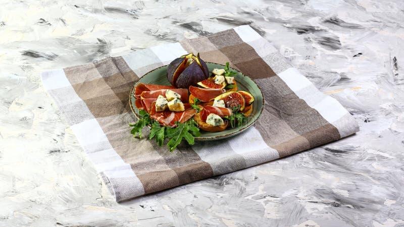 Piatto dei panini con i fichi, il formaggio blu ed il prosciutto di Parma sul tavolo da cucina Disposizione piana, spazio della c immagine stock