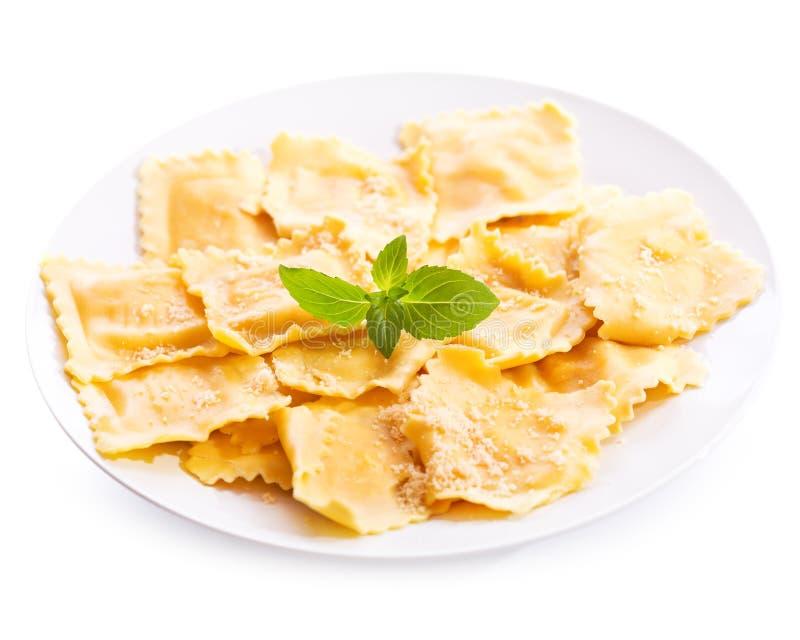 Piatto dei ravioli con basilico su fondo bianco fotografia stock