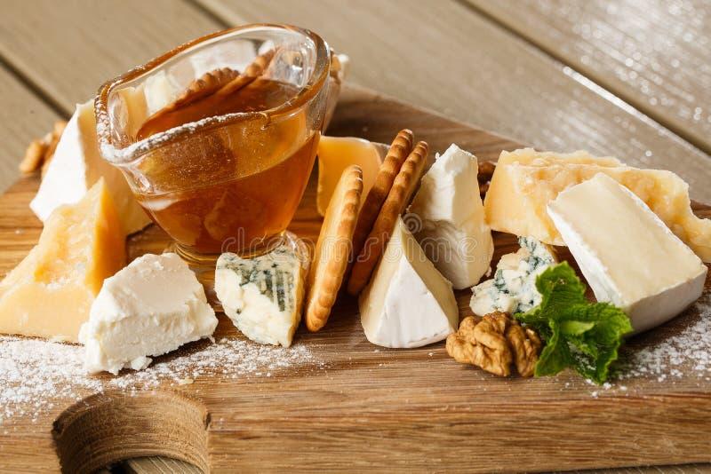 Piatto del formaggio dell'assaggio su un piatto di legno Alimento per vino e romantico, specialit? gastronomiche del formaggio su fotografia stock