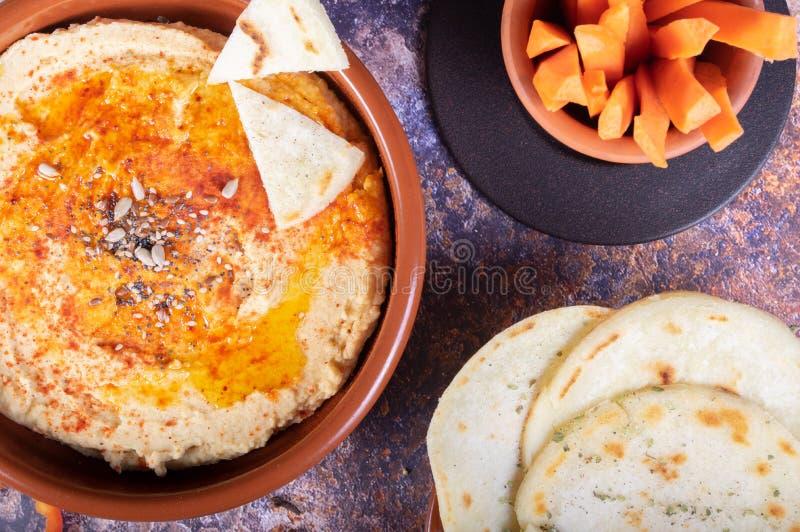 Piatto del hummus con pane indù e crudités della carota e del pepe Alimento del vegetariano e del vegano immagine stock libera da diritti