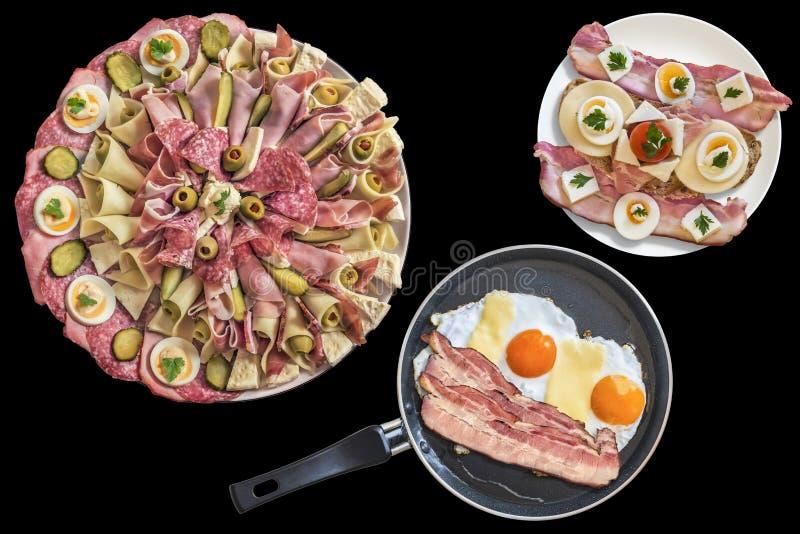 Piatto dell'aperitivo con Fried Eggs Bacon e formaggio in padella con le fette di lardo gastronomiche del bacon e del panino isol fotografia stock libera da diritti
