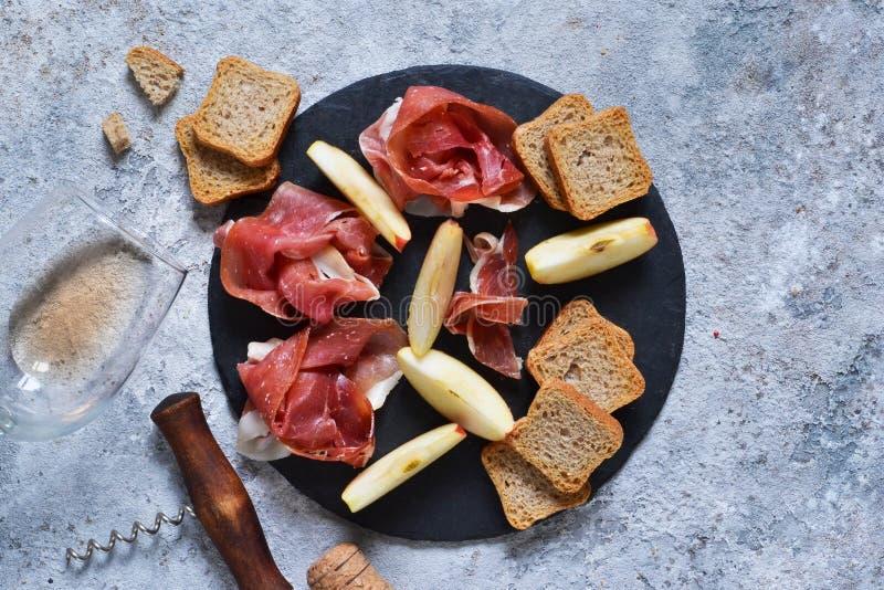 Piatto dell'ardesia con le squisitezze: jamon, formaggio blu, brie e un vetro di vino rosato Vista da sopra fotografia stock