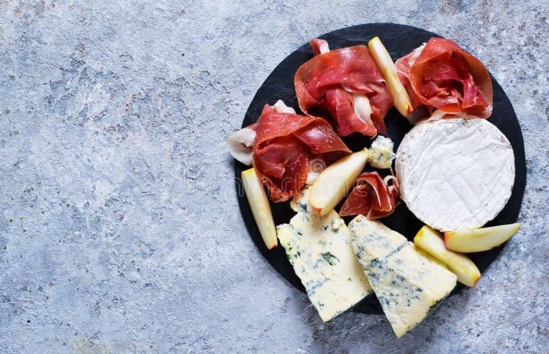 Piatto dell'ardesia con le squisitezze: jamon, formaggio blu, brie Vista da sopra immagine stock