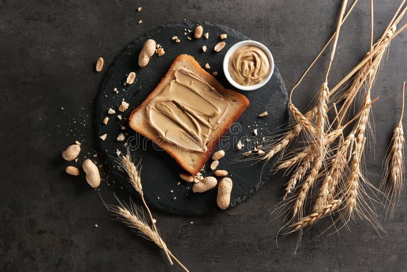 Piatto dell'ardesia con pane tostato e burro di arachidi saporiti sulla tavola fotografia stock