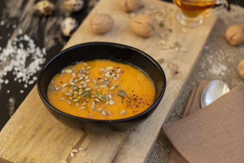 Piatto della minestra della zucca sul tagliere di legno immagine stock libera da diritti