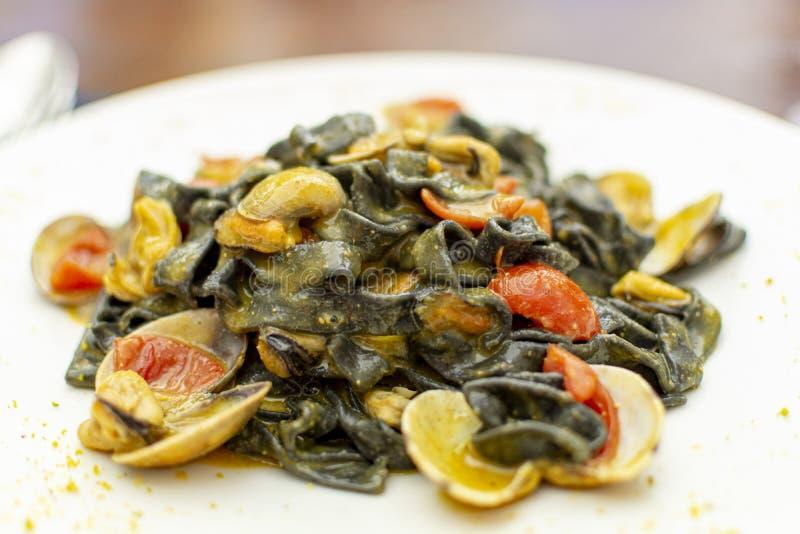 Piatto della pasta dei frutti di mare, fettuccini nero italiano con le vongole del vongole e cozze fotografia stock