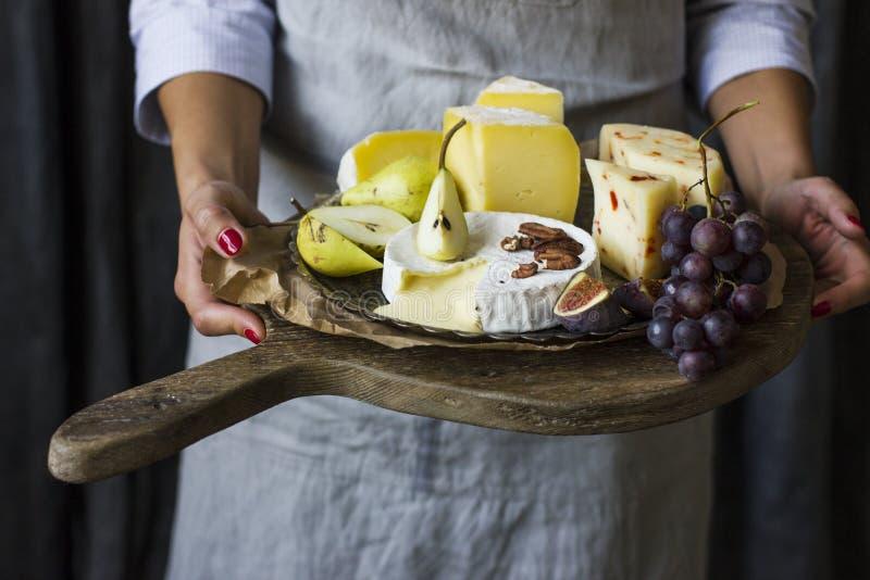 Piatto della tenuta della giovane donna di formaggio sul bordo di legno fotografie stock libere da diritti