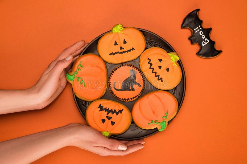 Piatto della tenuta della donna dei biscotti di Halloween fotografia stock libera da diritti
