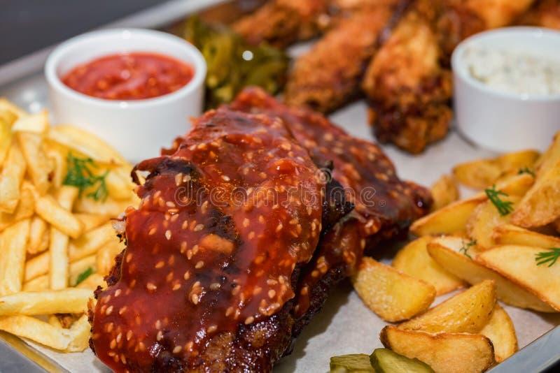 Piatto delle carni miste Le costole grigliate, ali di pollo sono servito con le patate fritte, i cunei ed il jalapeno immagini stock