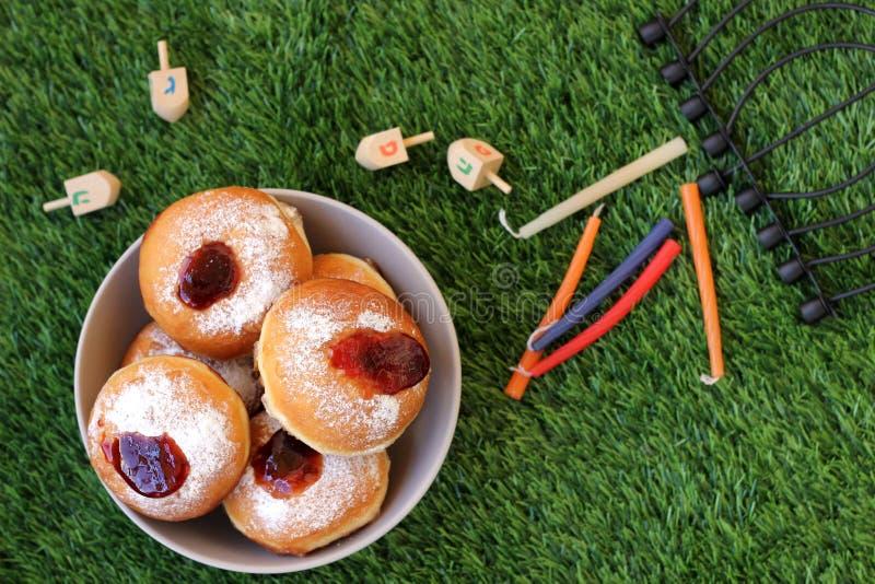 Piatto delle ciambelle e degli oggetti di Chanukah fuori su un backgro dell'erba immagine stock libera da diritti