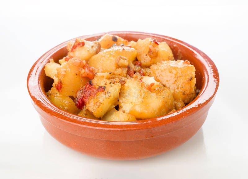 Piatto delle terraglie delle patate stufate con i peperoni su bianco fotografie stock libere da diritti