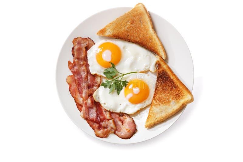 Piatto delle uova fritte, del bacon e del pane tostato isolati su backgroun bianco fotografie stock libere da diritti