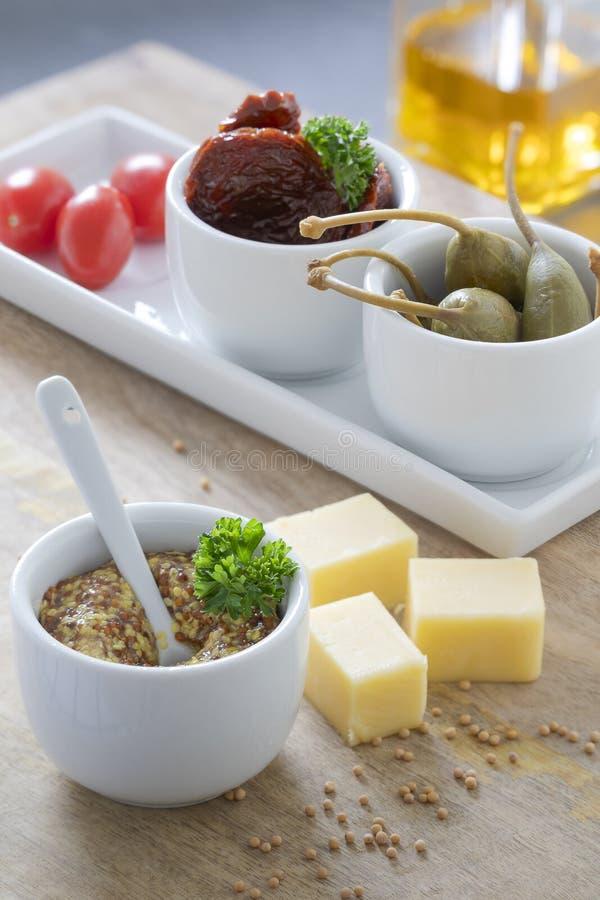 Piatto dello spuntino e semplici con formaggio, capperi della senape e pomodori saporiti immagine stock libera da diritti