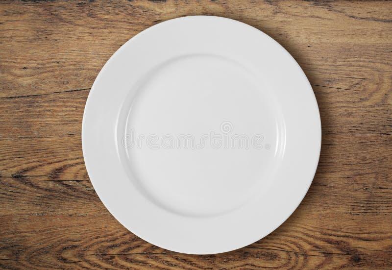 Piatto di cena bianco sulla vista di legno del piano d'appoggio fotografie stock