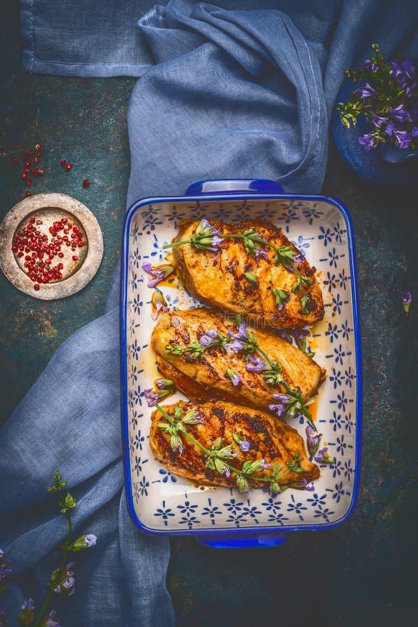 Piatto di cottura con il seno di Honey Glazed Chicken e condimento fresco sul fondo rustico scuro fotografia stock