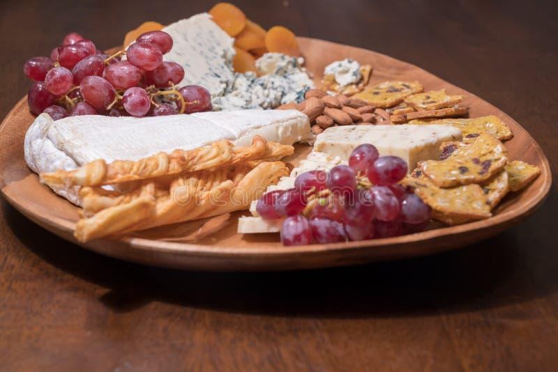 Piatto di formaggio con frutta ed i dadi immagini stock libere da diritti