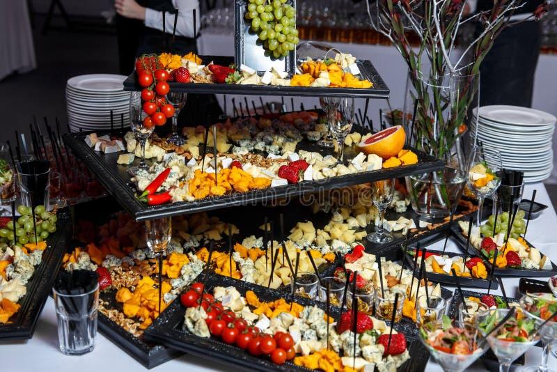 Piatto di formaggio con varietà di aperitivi sulla tavola su approvvigionamento di evento fotografia stock libera da diritti